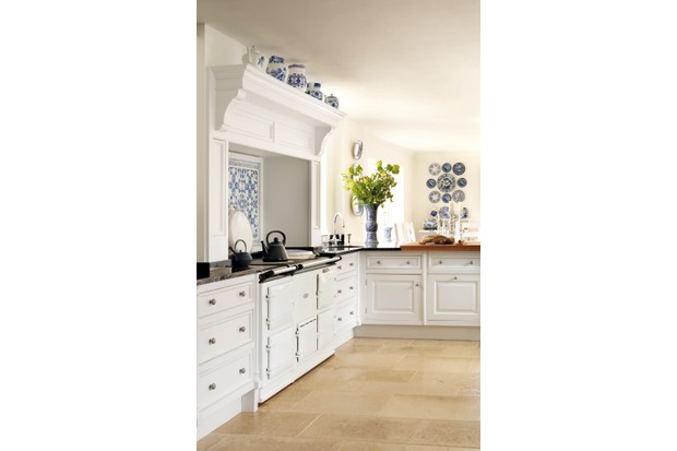 A classic white kitchen with an Aga and a display of blue and white ceramics