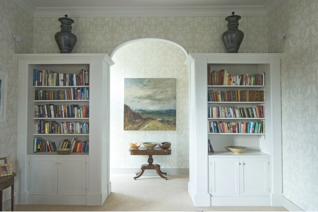 A wallpapered archway flanked by two white bookcases