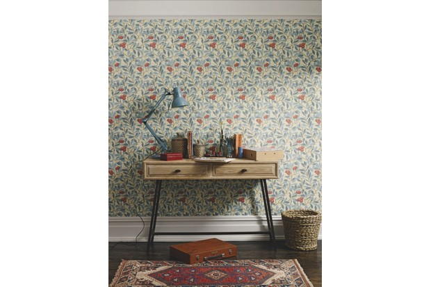 A wooden console table in front of William Morris wallpaper