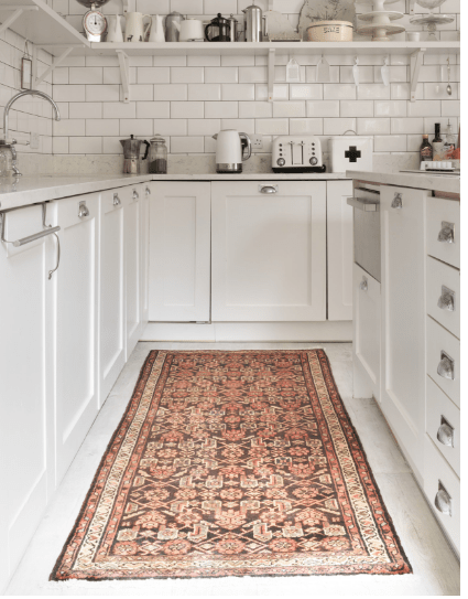 A contemporary white kitchen with an antique Persian rug on the floor