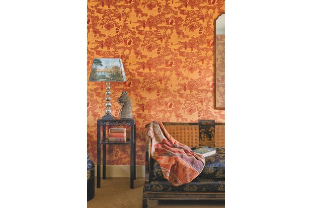 A classical living room decorated in orange and red Oriental wallpaper