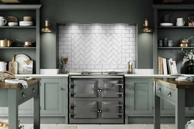 A sage green kitchen with Herringbone tiles and a grey Everhot range