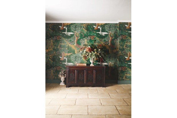 A hallway with a sideboard decorated in dark green chinoiserie wallpaper