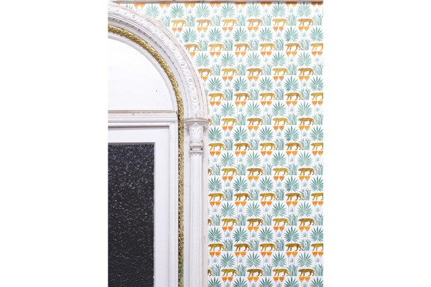 An archway decorated in wallpaper featuring palm leaves and cheetahs