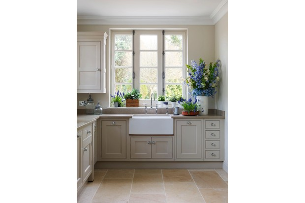 A beige kitchen with a ceramic sink and vases of fresh flowers