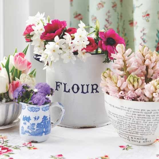 A collection of vintage bowls, vases and jugs filled with spring flowers.