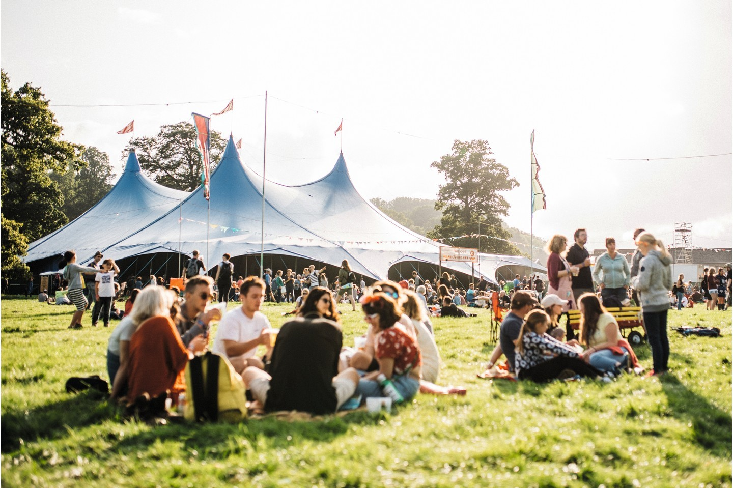 Groups of festival-goers sit under large tents in the sunshine at Green Man 2017