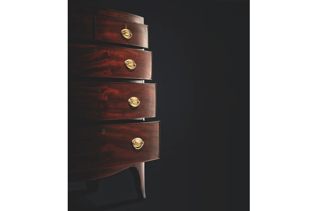 A side-on shot of a Georgian bow-fronted chest of drawers against a black background