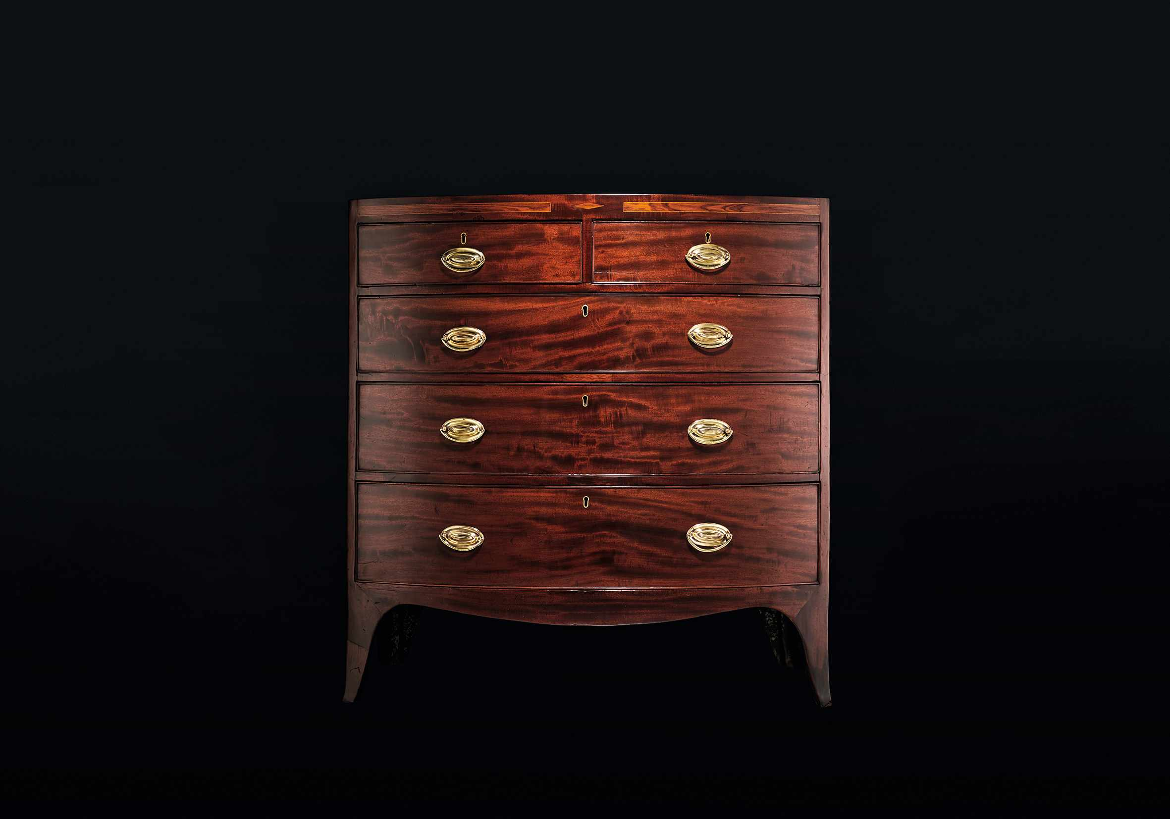 A shiny Georgian bow-fronted chest of drawers against a black background