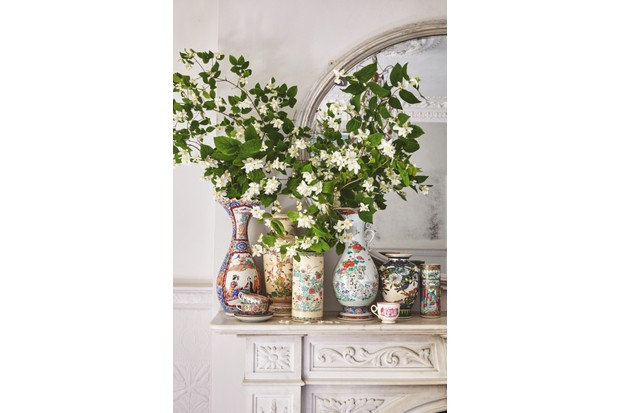 Japanese ceramic vases filled with tall white flowers and green foliage