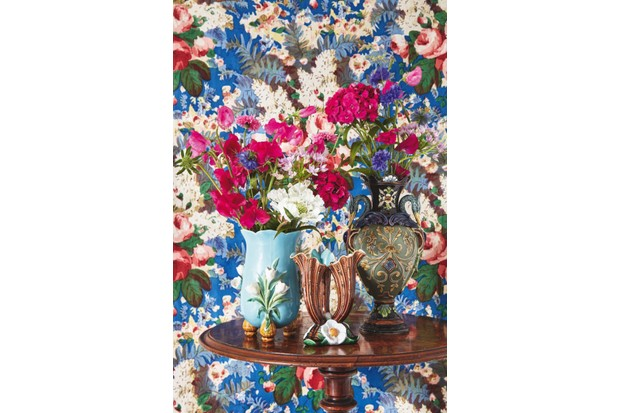 Majolica Vases filled with red and white flowers against a bold floral wallpaper
