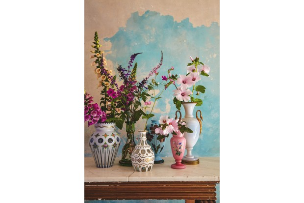 Bohemian enamelled glass vases filled with tall foxgloves against an exposed plaster wall