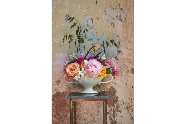 Constance spry vases filled with short peonies in front of an exposed plaster wall