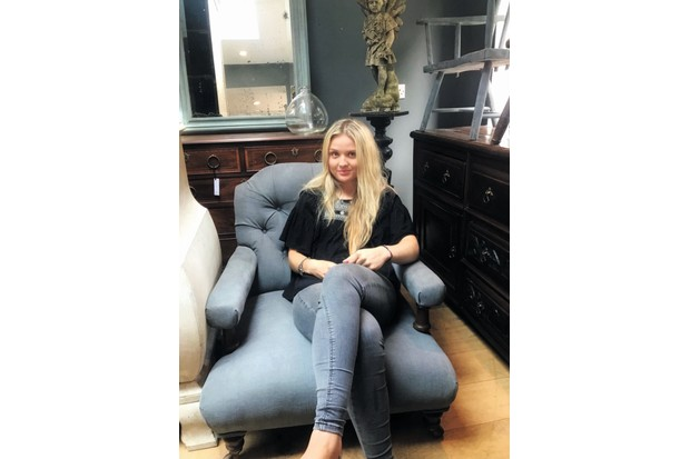 Antiques dealer Lily Johnston sat on a reupholstered Victorian armchair in her showroom