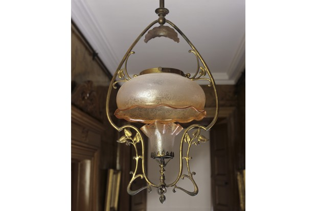 A brass 'harp' gas pendant of Art Nouveau design in a passage at The Argory. The etched glass shades and the smoke consumer are original. A gas tap can be seen at the base of the fitting.