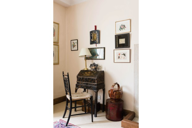 An eclectic display of antique prints above an antique Chinese bureau