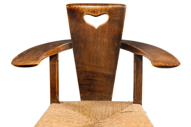 An antique wooden chair with a woven seat