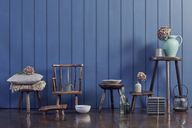Rustic-style furniture against a panelled blue wall