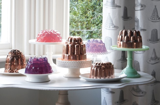 An array of jellies and antique jelly moulds on a while table in front of a window
