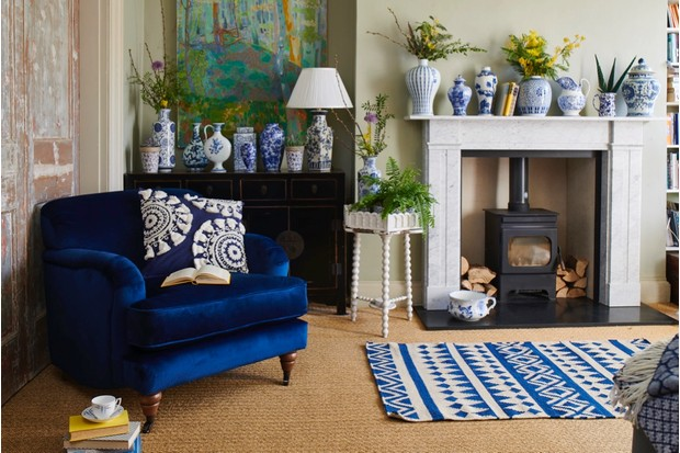 Stunning white and blue ceramics displayed on a mantelpiece beside a blue velvet armchair