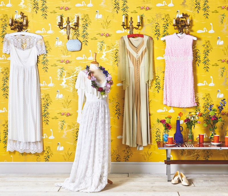 An array of vintage dressers hanging in front of bold yellow wallpaper
