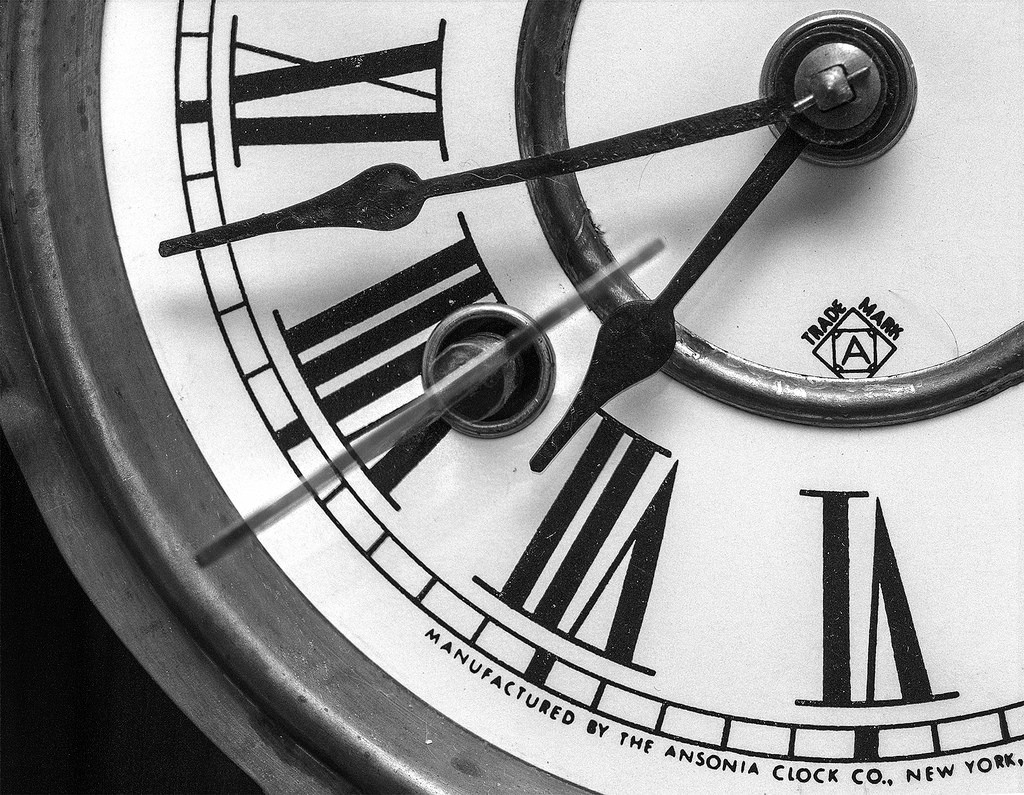 A vintage clock face with Roman numerals and hands in focus