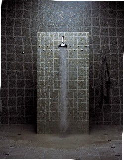 A shower with a dark ceramic wall
