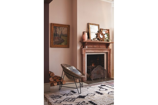 A wicker chair sits on an Aztec patterned rug in front of blush pink walls