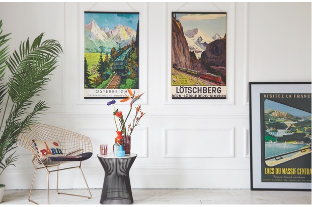 Posters of different places around the world are hung up on the wall