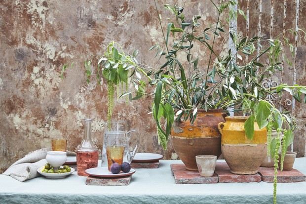 A distressed effect design on the wallpaper and some pots sat on a table in front of the wall