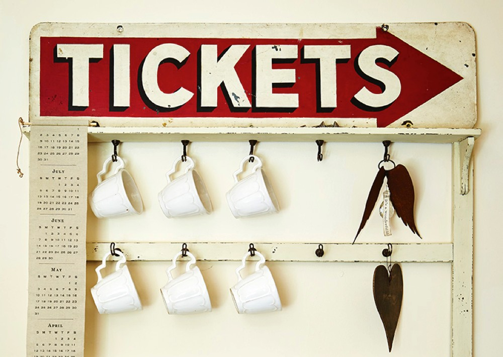 A vintage ticketing sign hanging above a rack of cups