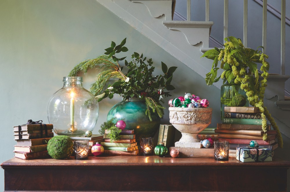 A display of vintage books, antique baubles, festive foliage and candles on a console table in a festive hallway.