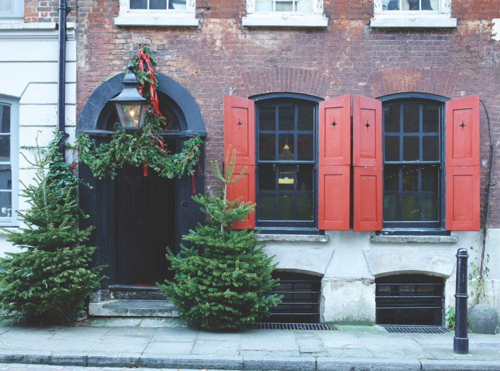 An image of the outside of Dennis Severs' House, featuring real Christmas trees and garlands