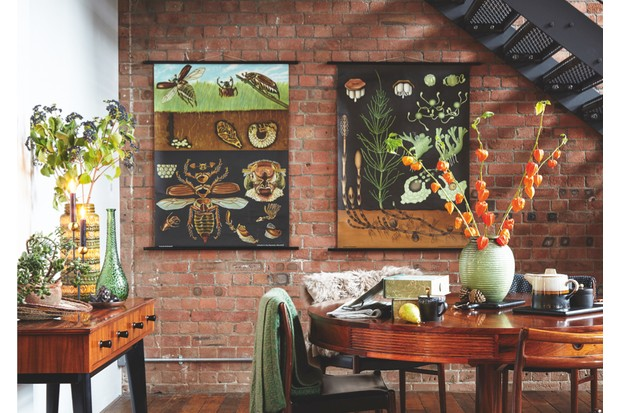 Dark graphic wall charts on a brick interior wall behind a mid-century dining set