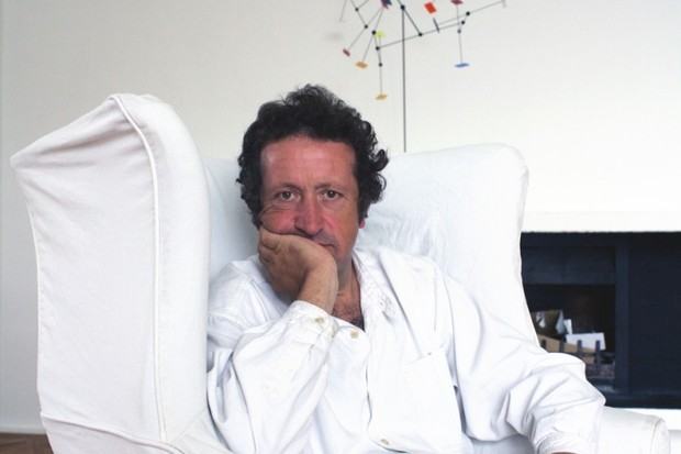 A portrait of artist Daniel Chadwick in a white armchair