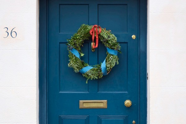 A navy blue front door with a green leafy wreath