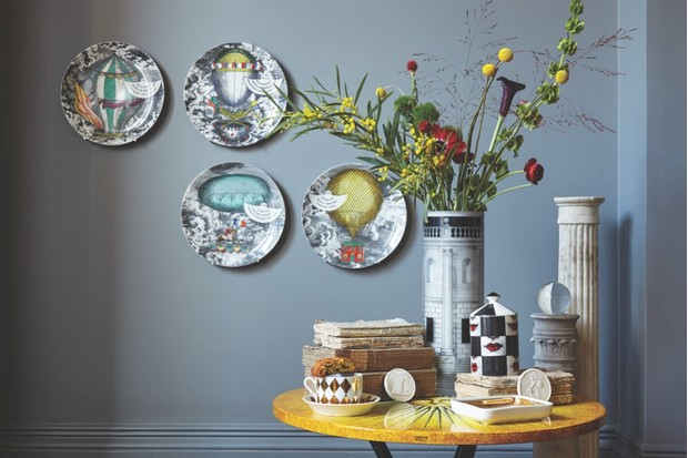 Decorative Fornasetti side plates displayed on a slate-grey wall