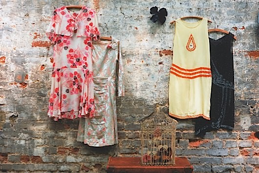 Vintage dresses hanging against a brick wall