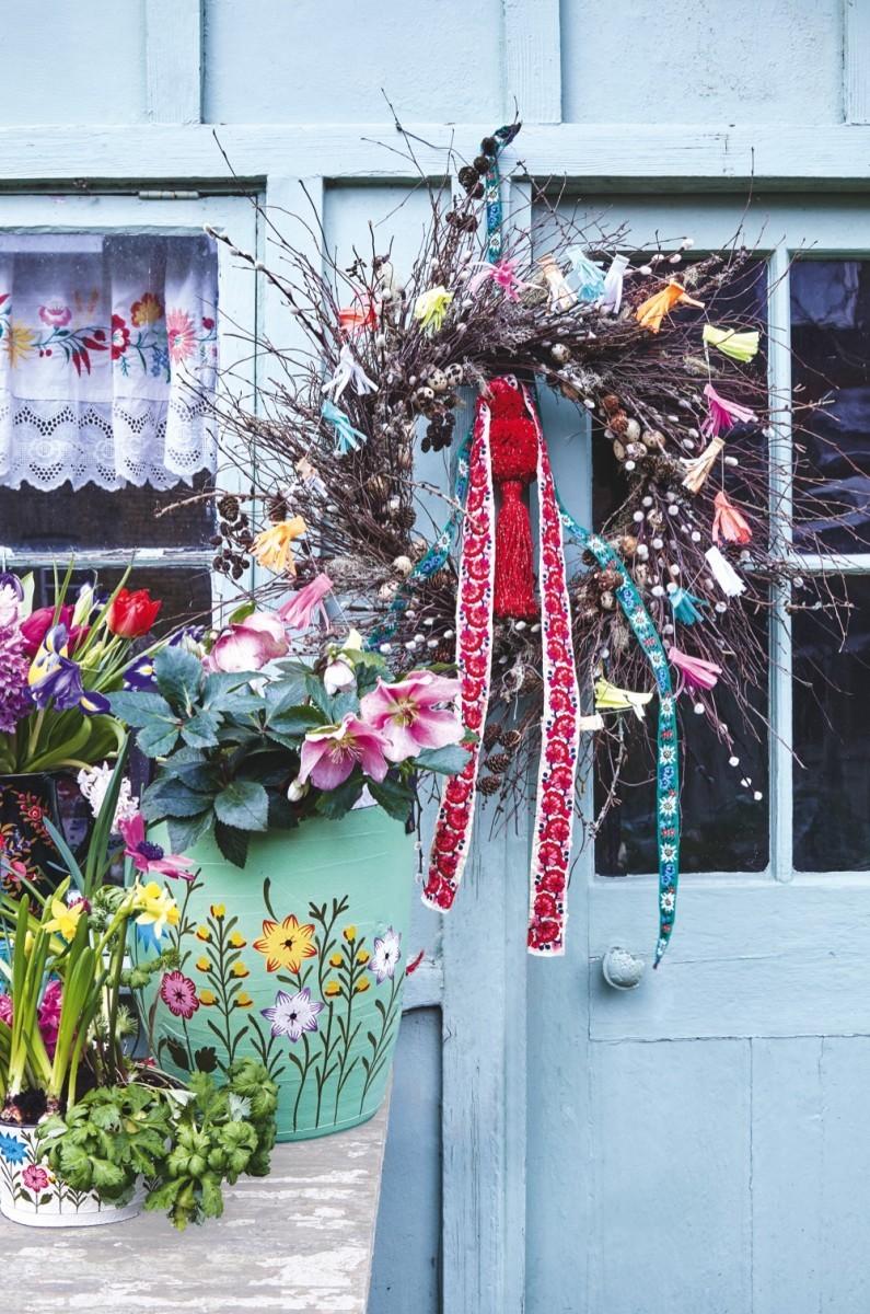 A vibrant Easter wreath on a blue door