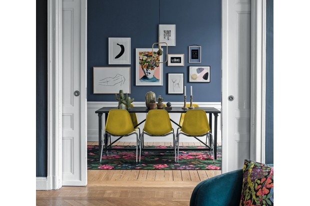 A gallery wall of modern prints on a dark blue wall behind a black dining room table with vintage yellow chairs