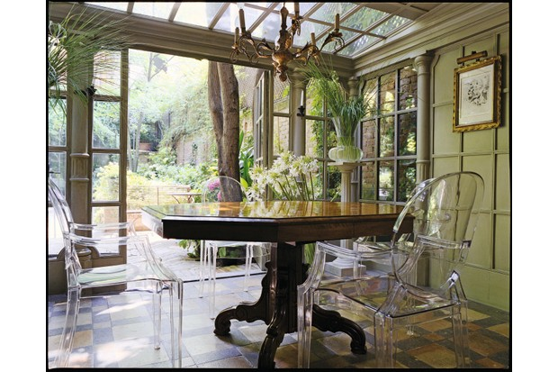 Three Louis Ghost Armchair around a mahogany table in a bright garden room