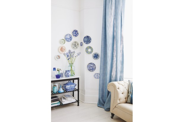 A swirl of blue and white china plates mounted on a white living room wall.