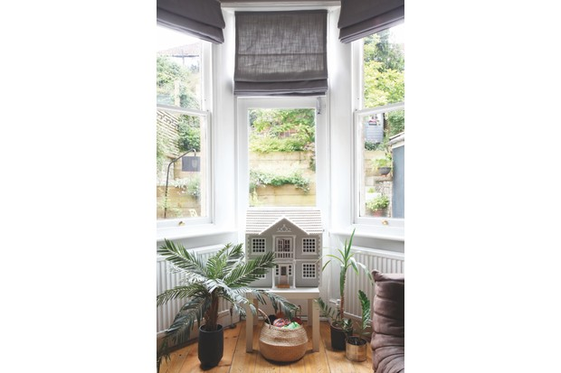 A bay window in Helen Ward's home featuring house plants and an ornate dolls house