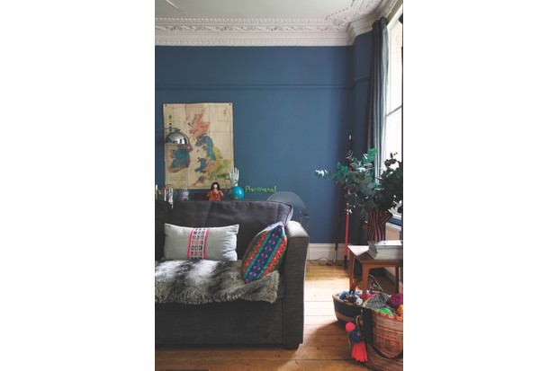 A slouchy grey sofa, a vintage map and vase of eucalyptus in Helen Ward's deep blue living room