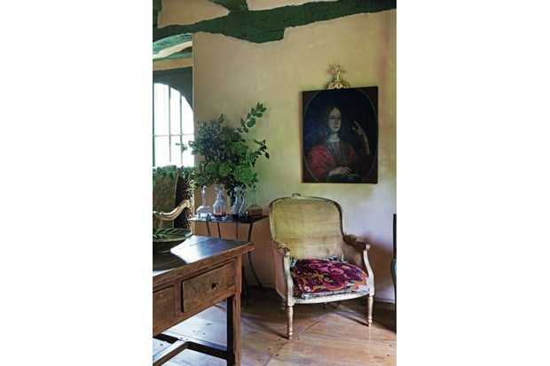 An antique armchair sits underneath a portrait painting