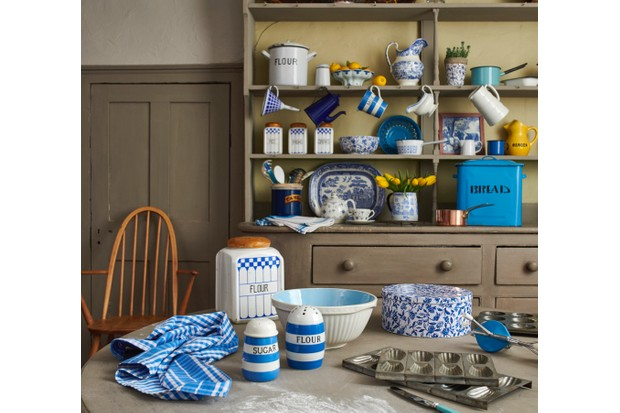 A kitchen dresser and table full of blue and white detailed platters, cups and saucers
