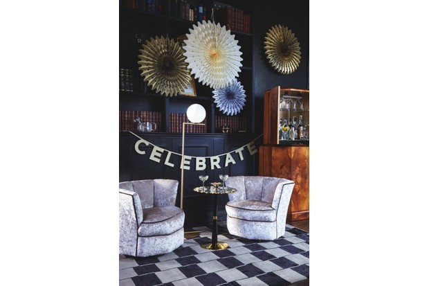 Two armchairs with two champagne bowls on a table between them. A 'Celebrate' banner hangs up behind the chairs