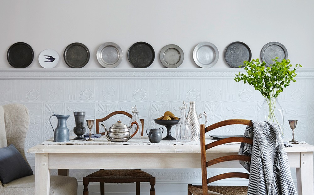 Antique pewter plates on show on a ledge above a kitchen table