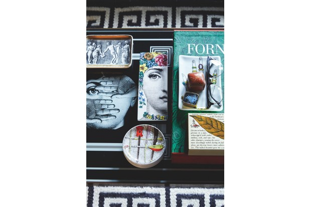 A black coffee table peppered with Fornasetti curios