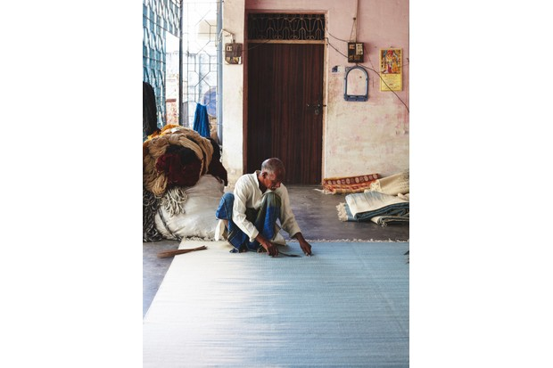 A man working on a flat weave rug
